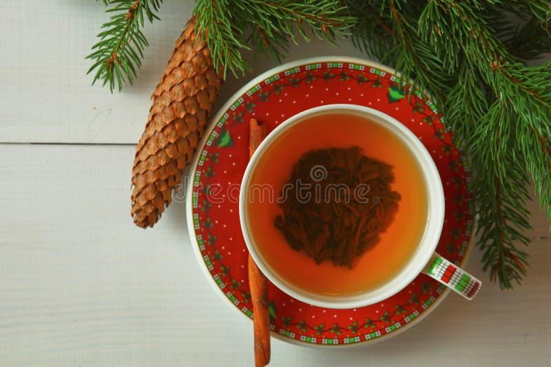 Fondo de la Navidad con las ramas de árbol de abeto, los conos, las decoraciones de la Navidad y la taza de té caliente de la fru fotografía de archivo