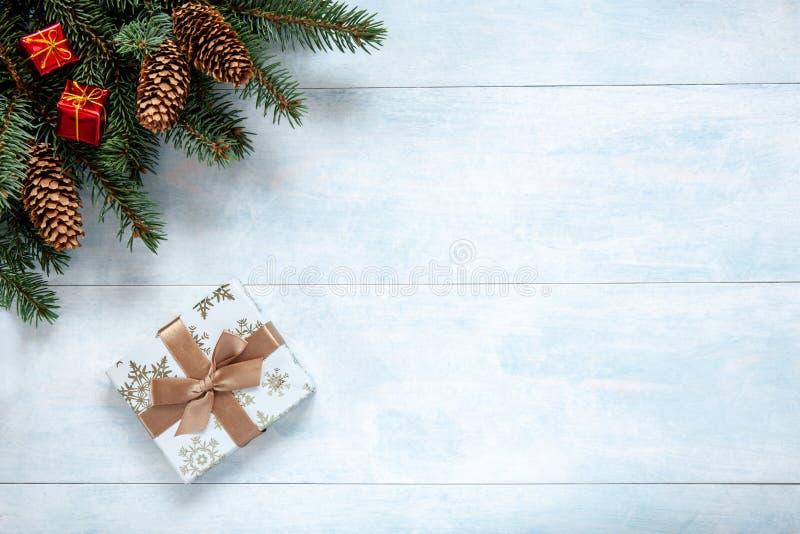 Fondo de la Navidad con las ramas de árbol de abeto, los conos y la caja de regalo fotos de archivo