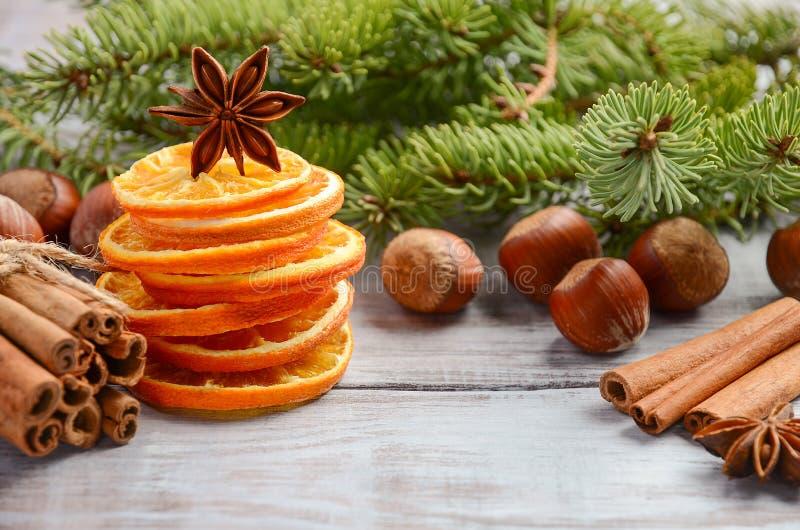 Fondo de la Navidad con las ramas del abeto, las nueces, las especias y las naranjas secadas imagen de archivo libre de regalías