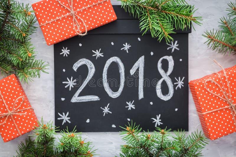 Fondo de la Navidad con las ramas del abeto, pizarra con 2018 y copo de nieve, cajas de regalo en la tabla concreta gris Visión s imágenes de archivo libres de regalías