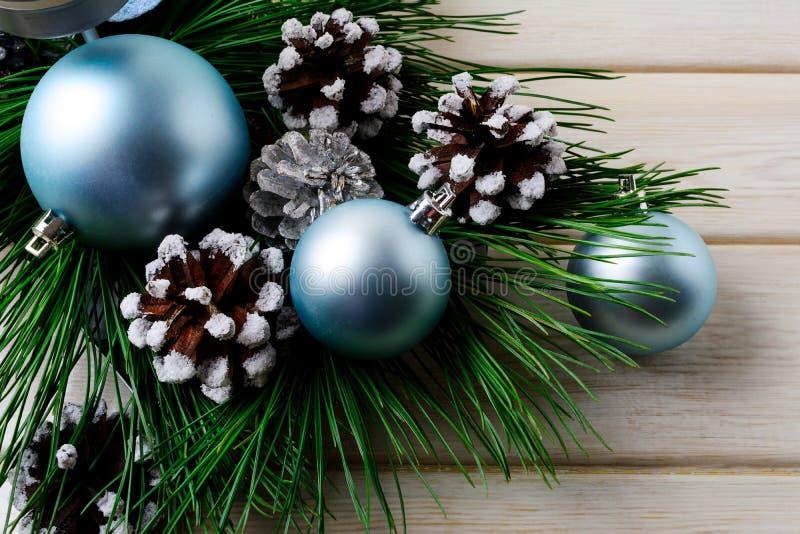 Fondo de la Navidad con los ornamentos azules y el cono adornado del pino imagenes de archivo
