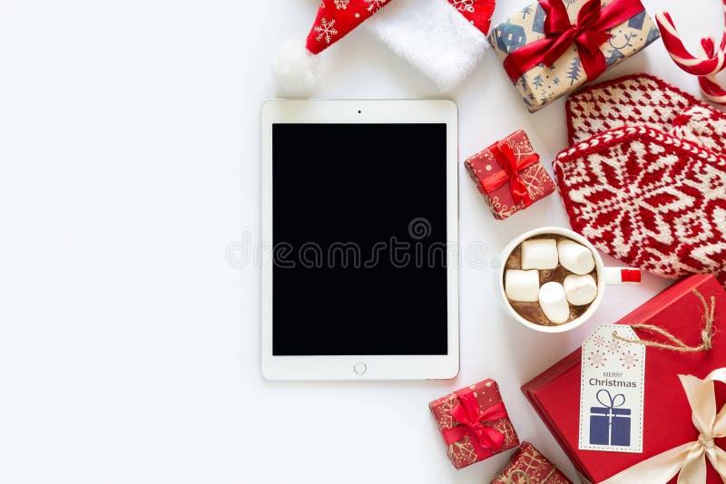 Fondo de la Navidad con los presentes hechos a mano envueltos en papel del arte, taza de chocolate caliente y tableta imagen de archivo