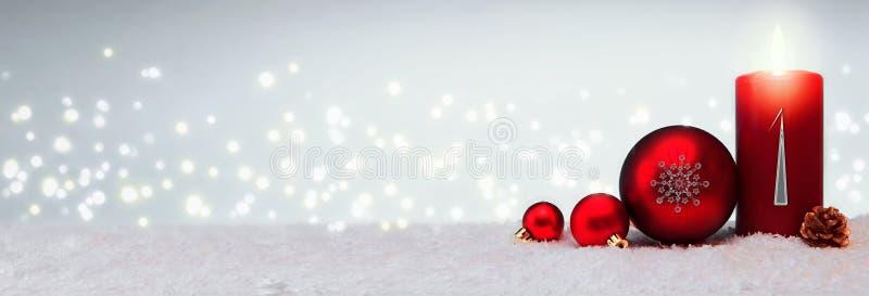 Fondo de la Navidad con la primera vela del advenimiento y la chuchería roja imágenes de archivo libres de regalías