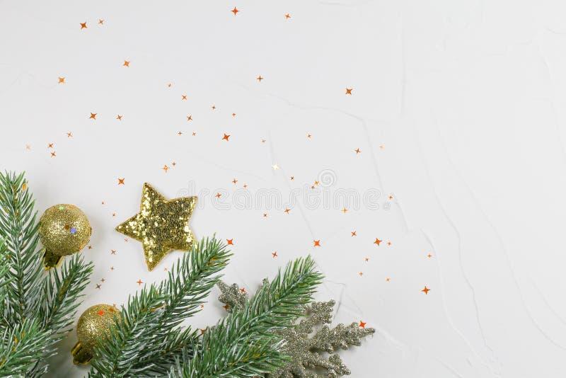 Fondo de la Navidad con la rama del abeto, bolas chispeantes de oro y una estrella en un fondo blanco foto de archivo libre de regalías