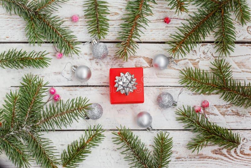 Fondo de la Navidad con con la rama del abeto y caja del rojo actual, bolas de plata en la tabla de madera blanca imágenes de archivo libres de regalías