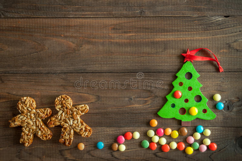 Fondo de la Navidad con una gragea del árbol y del chocolate del juguete en fondo de madera foto de archivo libre de regalías