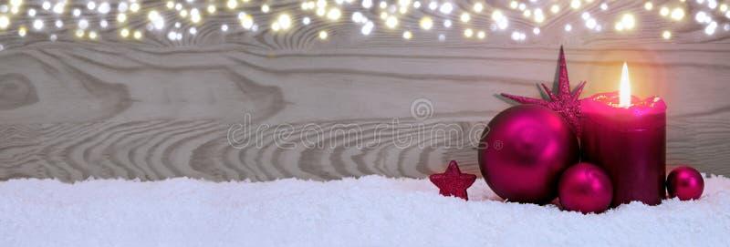 Fondo de la Navidad con la vela del advenimiento y la chuchería rosada fotografía de archivo
