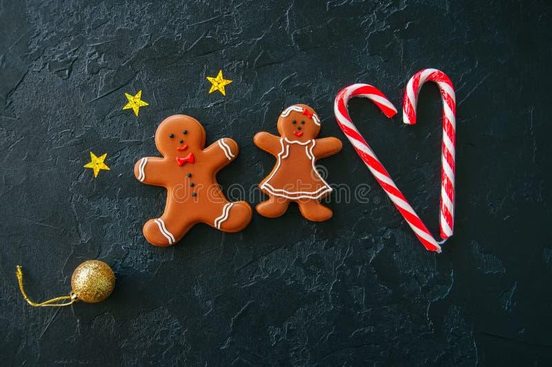 Fondo de la Navidad, hombre de pan de jengibre y galletas festivos de la muchacha, foto de archivo