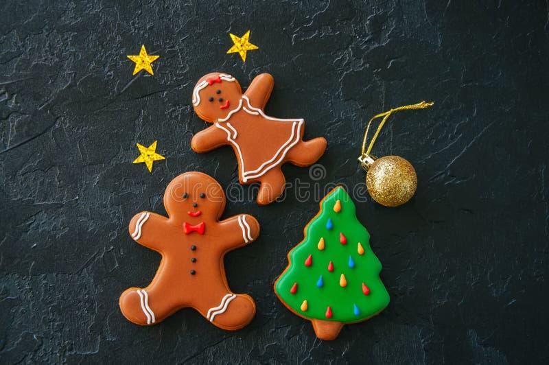 Fondo de la Navidad, hombre de pan de jengibre y galletas festivos de la muchacha, imagen de archivo libre de regalías