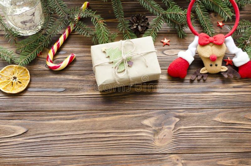 Fondo de la Navidad: juegue los ciervos, caja de regalo, abeto, caramelo en la tabla de madera imágenes de archivo libres de regalías
