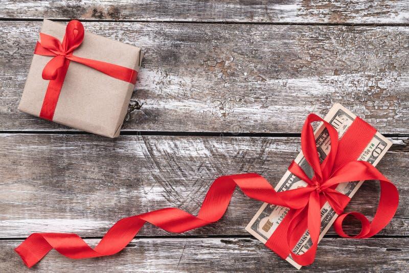 Fondo de la Navidad de la madera vieja, del dinero embellecido con la holgura roja y del regalo Visión superior fotos de archivo