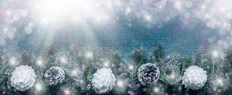 Fondo de la Navidad Nevado, ramas de árbol de abeto con los conos del pino y chucherías de Navidad en fondo de madera imagen de archivo libre de regalías