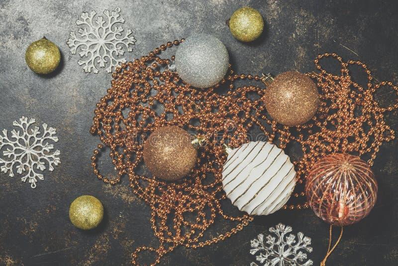 Fondo de la Navidad, oro y bolas de plata, gotas, copos de nieve en un fondo rústico Decoraciones hermosas del vintage para fotos de archivo