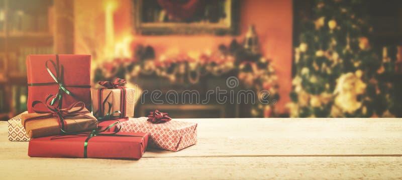 fondo de la Navidad - regalos envueltos en la tabla en el cuarto fotografía de archivo