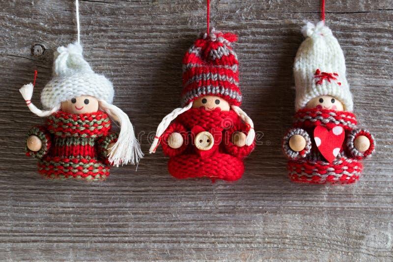 Fondo de la Navidad - tres figuras lindas en suéteres calientes Han fotos de archivo libres de regalías