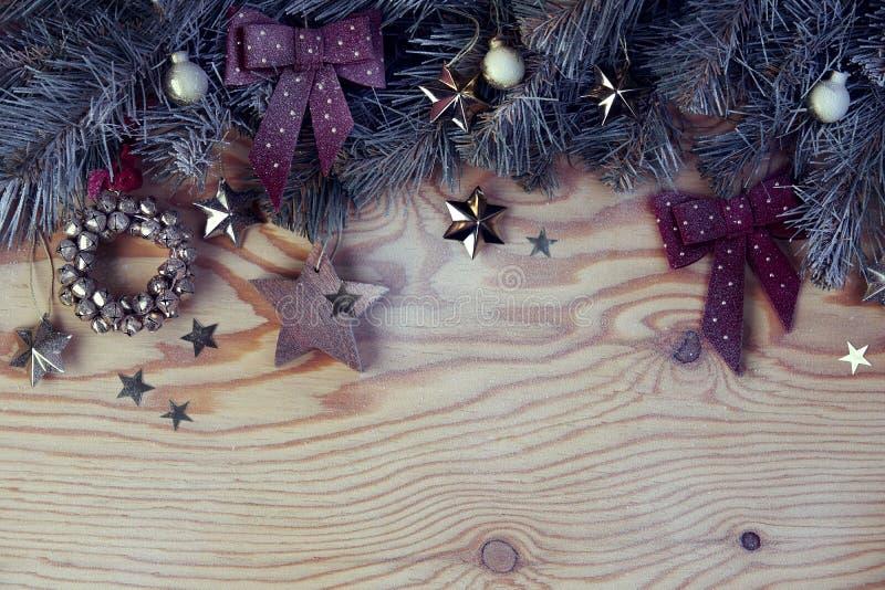 Fondo de la Noche Vieja de la Navidad con el árbol de abeto debajo de la nieve y decoración en el tablero de madera ligero foto de archivo libre de regalías