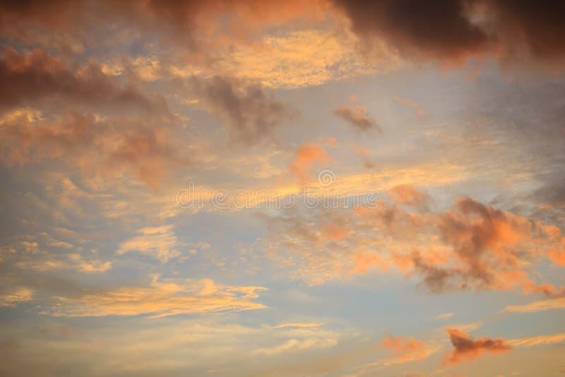 Fondo de la nube roja y del cielo azul El cielo dramático de la puesta del sol comenzó a cambiar de azul a la naranja fotografía de archivo