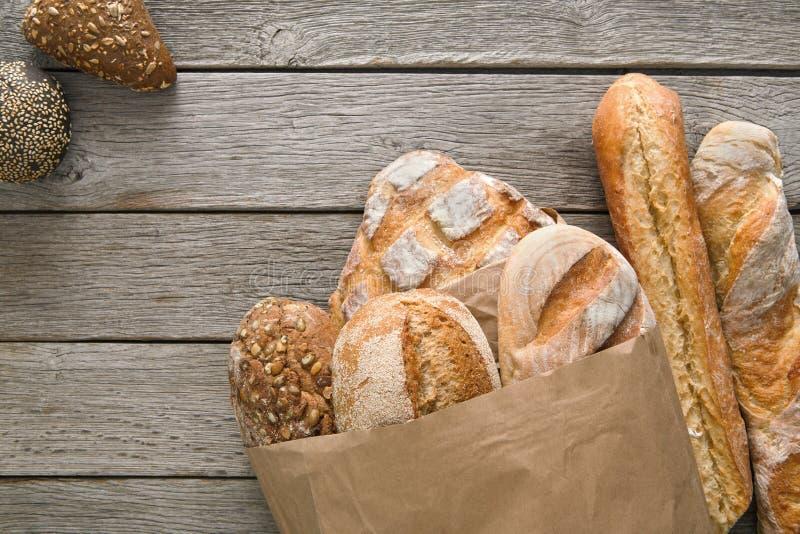Fondo de la panadería del pan Brown y composición blanca de los panes del grano del trigo en la madera rústica imagen de archivo