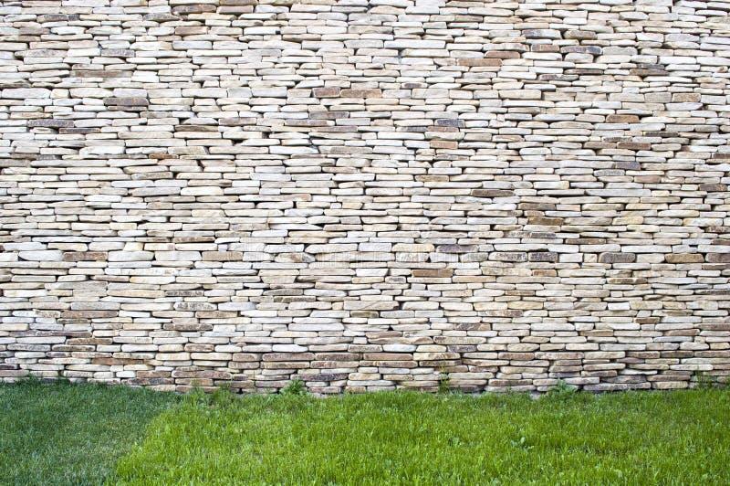 Fondo de la pared de piedra con la hierba fotos de archivo