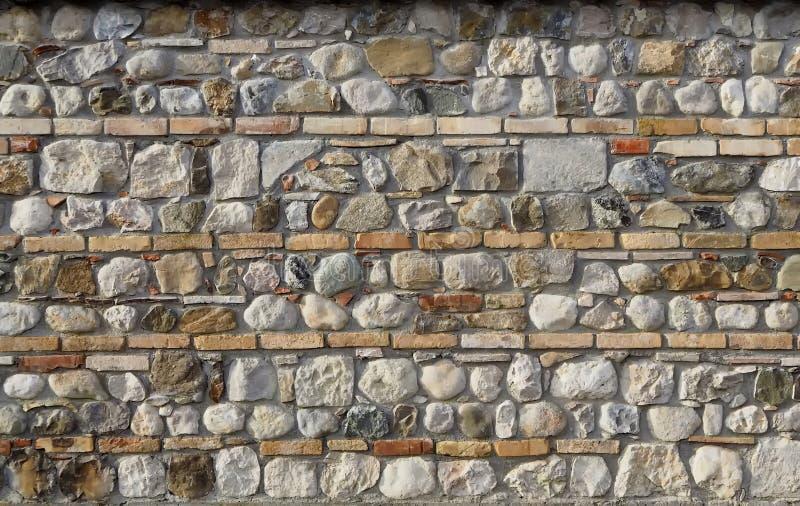 Fondo de la pared Piedras naturales entremezcladas con las líneas de ladrillos horizontales fotos de archivo libres de regalías