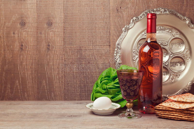 Fondo de la pascua judía con la botella de vino, el matzoh, el huevo y la placa del seder fotos de archivo
