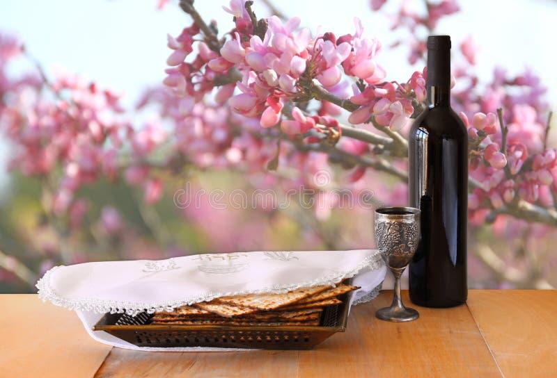Fondo de la pascua judía vino y matzoh (pan judío del passover) en la tabla de madera imagen de archivo libre de regalías