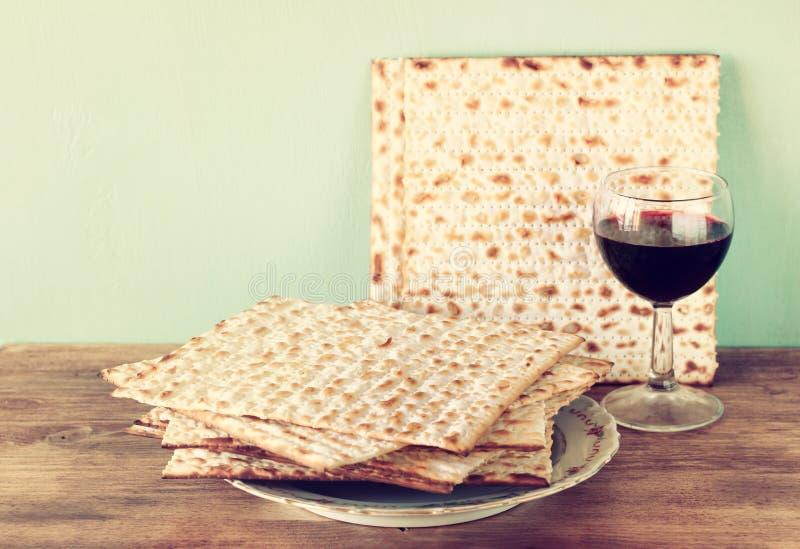 Fondo de la pascua judía. vino y matzoh (pan judío del passover) sobre fondo de madera. fotografía de archivo