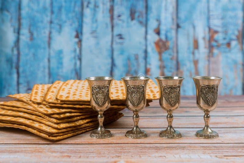 Fondo de la pascua jud?a cuatro vidrios pan jud?o del d?a de fiesta del vino y del matzoh sobre el tablero de madera imagen de archivo