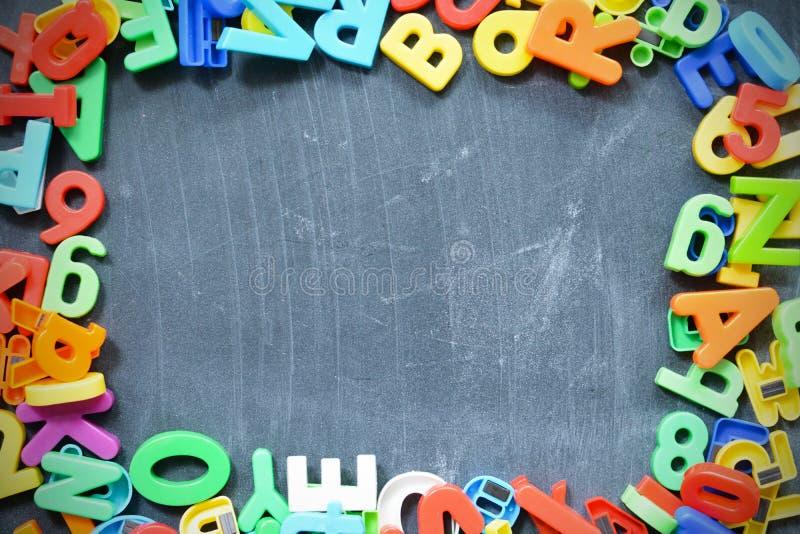 Fondo de la pizarra con los bloques coloreados de la letra como marco fotos de archivo
