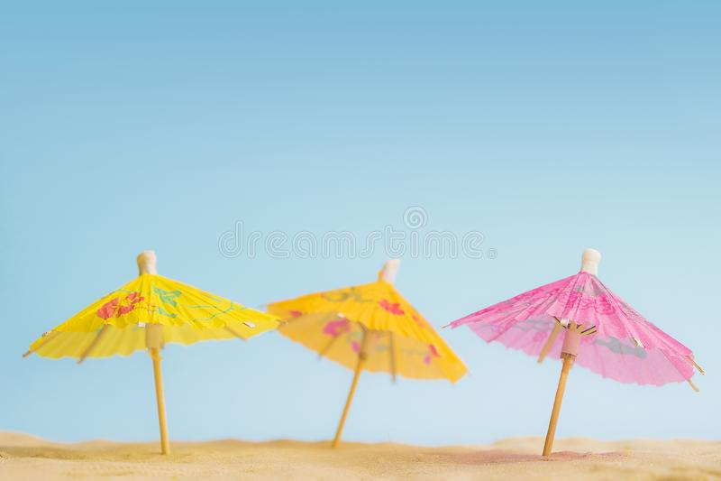 Fondo de la playa con los parasoles de playa coloridos en la arena Vacaciones de verano y concepto del viaje Bandera tropical del imagen de archivo libre de regalías