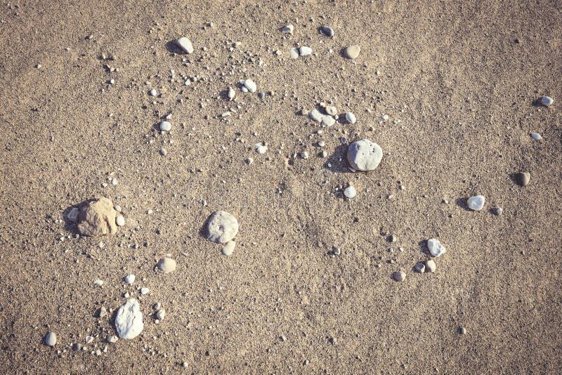 Fondo de la playa de Sandy con un puñado de pequeñas piedras fotografía de archivo libre de regalías