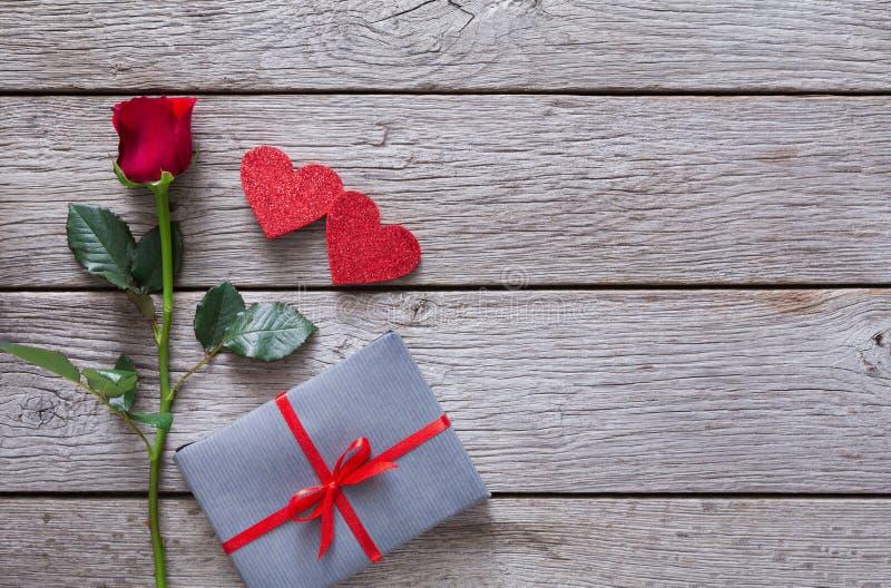 Fondo de la tarjeta del día de San Valentín con la flor de la rosa del rojo, los corazones de papel y la actual caja en la madera imagenes de archivo