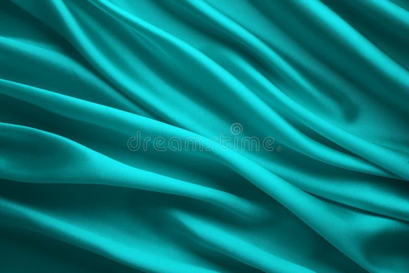 Fondo de la tela de seda, ondas azules del paño del satén, materia textil que fluye abstracta fotografía de archivo