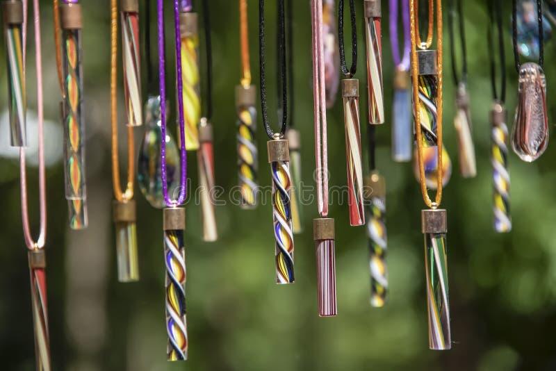 Fondo de la variedad de cuentas de cristal sopladas coloridas que cuelgan contra un contexto verde del bokeh - foco bajo fotos de archivo libres de regalías