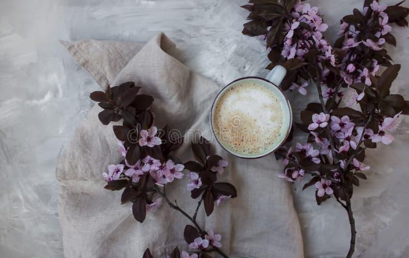 Fondo de la visión superior de flores rosadas en colores pastel y de una taza de café caliente fotografía de archivo