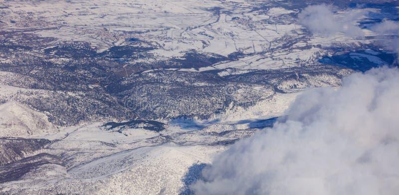 Fondo de las montañas Nevado y nubes blancas sobre ellos Foto aérea de la ventana plana del ` s foto de archivo libre de regalías
