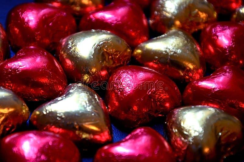 Fondo de los caramelos de chocolate bajo la forma de primer de los corazones Rojo y empaquetado del oro hecho de hoja brillante imagenes de archivo