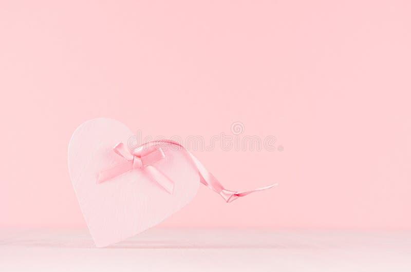 Fondo de los día de San Valentín - corazón decorativo rosado en colores pastel elegante con la cinta en el tablero de madera blan fotografía de archivo