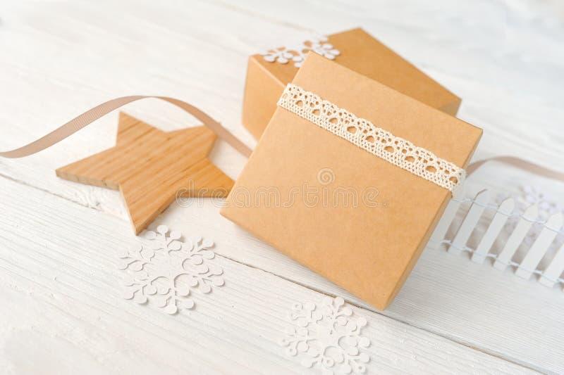Fondo de los días de fiesta de la Navidad con las decoraciones y las cajas de regalo festivas en el tablero de madera blanco con  imagen de archivo