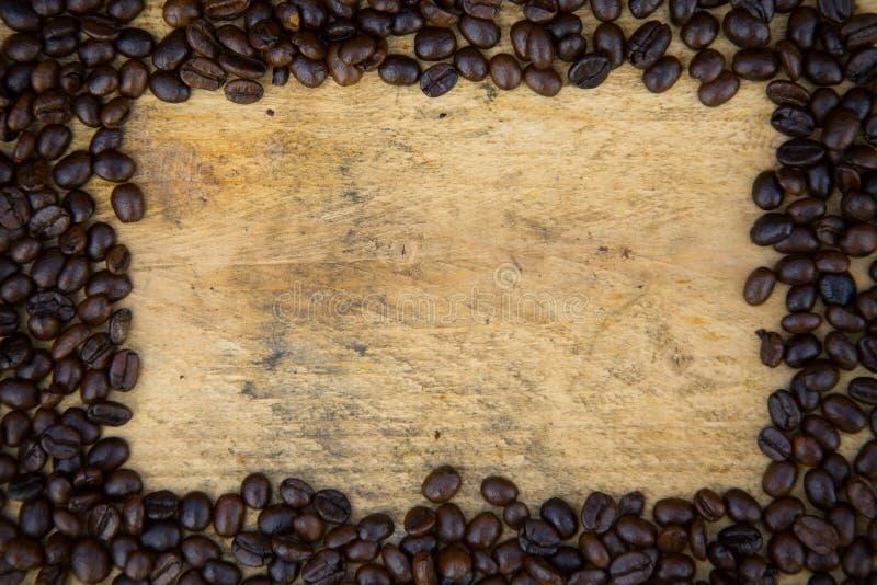 Fondo de los granos de café en los granos de café de madera, frescos con la taza de café en el fondo de madera, fondo determinado imágenes de archivo libres de regalías