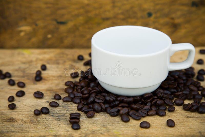 Fondo de los granos de café en los granos de café de madera, frescos con la taza de café en el fondo de madera, fondo determinado foto de archivo libre de regalías