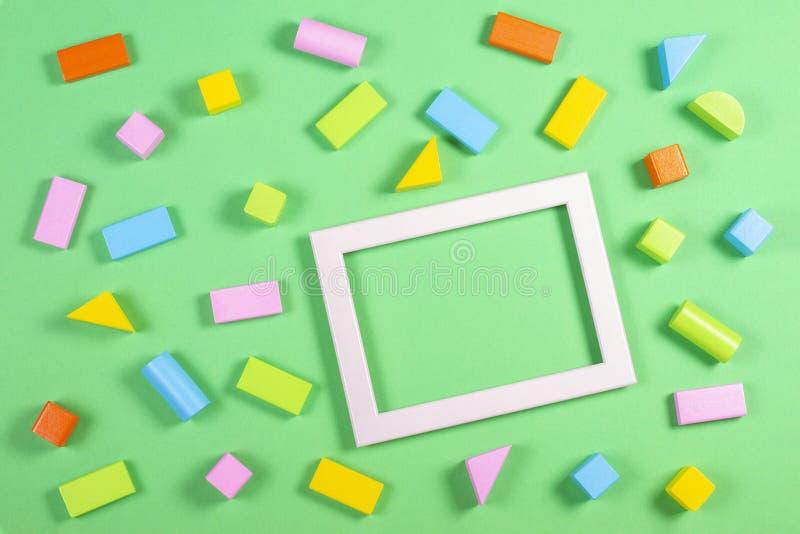 Fondo de los juguetes con el marco vacío de la imagen de la foto y modelo de madera colorido de los cubos en fondo del color verd foto de archivo