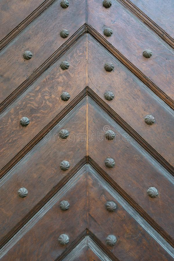 Fondo de los tablones de madera plegados en dirección de la flecha, cosido con los pernos negros del metal con una cabeza tallada foto de archivo