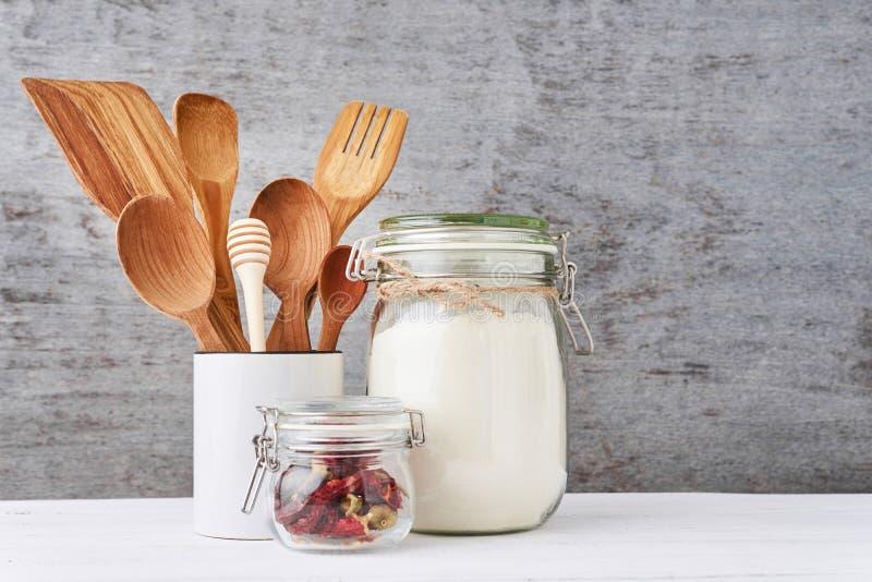 Fondo de los utensilios de la cocina con los cubiertos de madera en taza de cerámica en una tabla blanca fotos de archivo