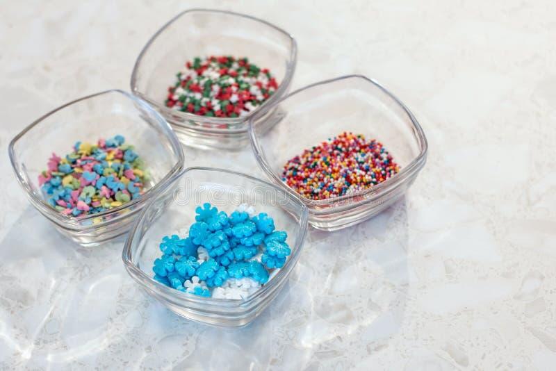 Fondo de mármol Cuatro tazas de cristal transparentes con las decoraciones para la confitería y la hornada fotografía de archivo libre de regalías