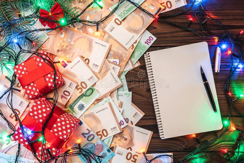 Fondo de madera, billetes de banco de diverso valor Muchos regalos, ramas del abeto, atmósfera de la Navidad imágenes de archivo libres de regalías