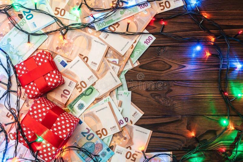 Fondo de madera, billetes de banco, regalos, ramas del abeto, atmósfera de la Navidad Visión superior foto de archivo libre de regalías