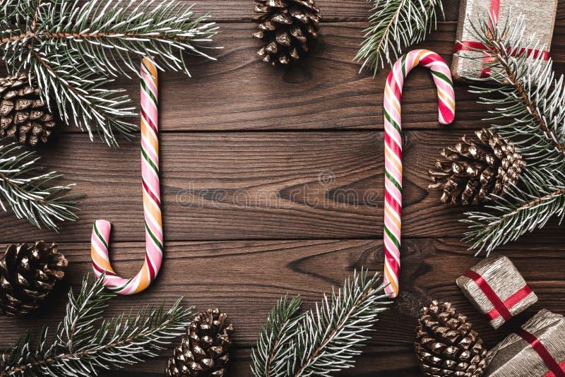 Fondo de madera de Brown Ramas del abeto, conos decorativos Caramelos coloridos Regalos para Navidad foto de archivo