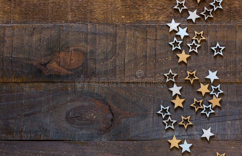 Fondo de madera con decoraciones navideñas de estilo rústico. Estrellas plateadas y doradas sobre fondo de madera antiguo con es foto de archivo