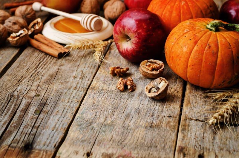 Fondo de madera con la calabaza, las manzanas, el trigo, la miel y las nueces fotografía de archivo